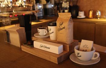 カフェキツネで使われるカップ、袋などが飾られています。奥に見えるのはエスプレッソマシーンです。