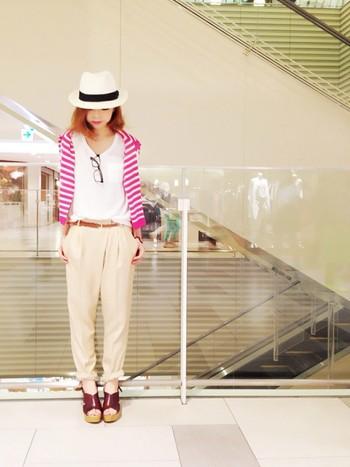 同じチノパンを使った別コーデスタイル。シンプルな白Tシャツに、黒縁メガネと帽子のカジュアル小物をあわせて。肩掛けのピンクのカーディガンが可愛いアクセントになっていますね。