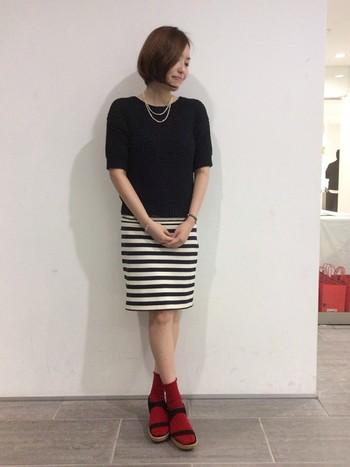 赤いソックスがアクセントになったコーディネイト。シンプルな服の着こなしの参考になりますね。
