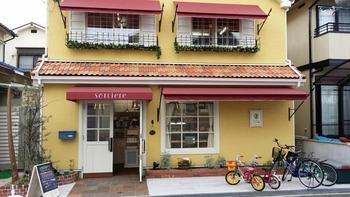 黄色い壁が目印。2階はイートインスペースでオーガニックコーヒーやロンネフェルトの紅茶をいただくことができます。