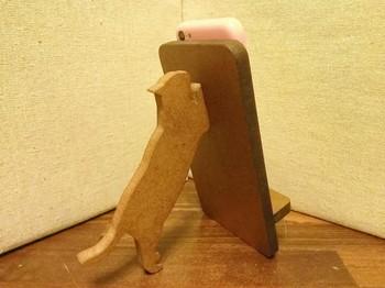 <猫が支える携帯・スマホスタンド>  猫が一生懸命スマホを支えてくれる木製のスタンドです。この作家さんは他にもたくさんの動物スタンドを制作されていますよ。ちゃんと充電用の穴があけてあるのも嬉しい!