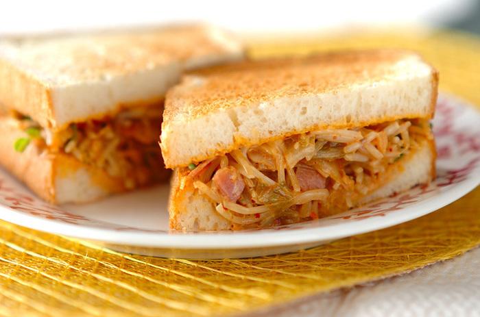 ゴマ油で炒めたモヤシ・貝われ菜・ベーコン・白菜キムチをトーストしたパンに挟めばシャキシャキもやしが美味しいピリ辛サンドの出来上がり♪ 味の決め手はマヨネーズ+ラー油! ビールにも合います。