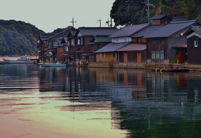 春の穏やかな海面は、伊根の舟屋と夕陽を映して。