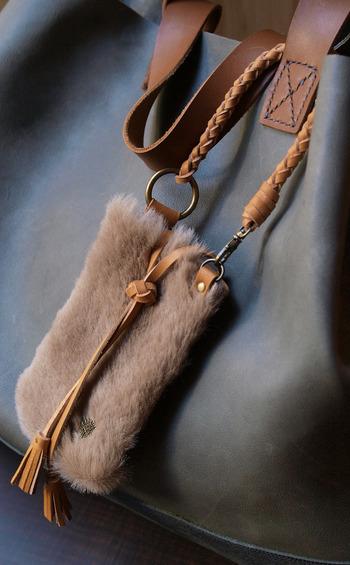 ムートンファーと牛革を使ったちょっとリッチで大人かわいいスマホケース。バッグの持ち手に付ける事ができるのも嬉しい。