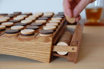 """世界的に有名なゲーム・リバーシも、木工作家のSOETACRAFTさんの手にかかれば素敵な木のおもちゃに。 黒石はウォールナット、白石はメープルの木で濃淡を表現されています。 遊んだ後は、石をボードの中の引き出しに収納可能。 美しい木の曲線や、オイル仕上げに""""職人の心""""を感じるすばらしい作品です。"""