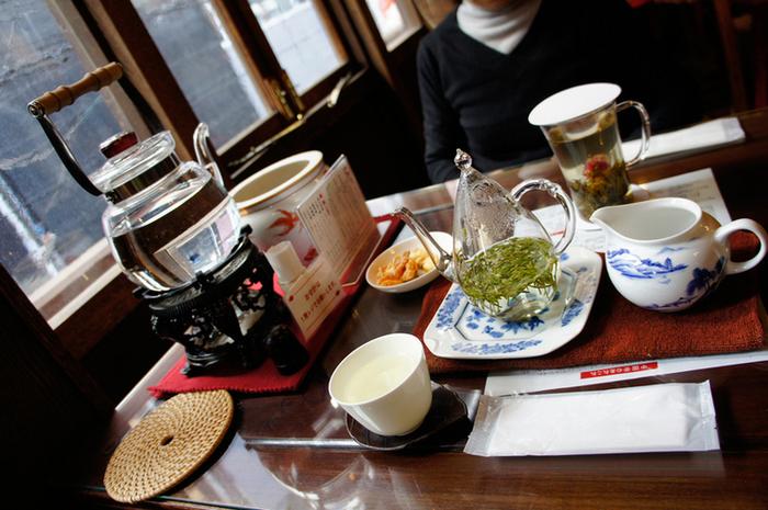 涙型で上部に丸く穴が開いたかわいらしいガラスポットの細長い茶葉のお茶。 卓上のポットからお湯を注ぎ、まず茶碗を温め、ガラスポットの中に茶葉を入れ、 茶碗にあったお湯をガラスポットへ入れ数分待ちます。 茶葉が少し広がってきたところが一煎目。 ガラスポットに入れたお茶を飲み切るのではなく、少なくなってきたら、 お茶が濃くなりすぎないようお湯を注ぎ足して、香りの強くなる二煎目を楽しむことができ、 様々な味わいを堪能できます。