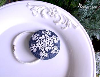 タティングレースで作った雪の結晶モチーフをデニム生地の上にのせたヘアゴム。直径5cmくらいのくるみボタンが中に入っています。