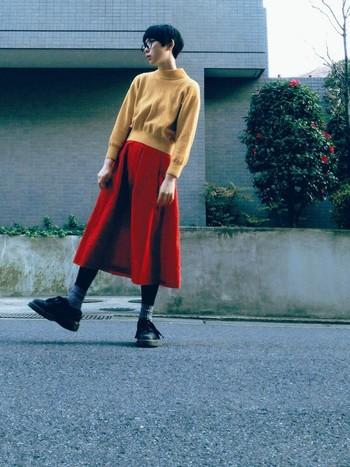 からし色のニットにビビットな赤色のスカートで。