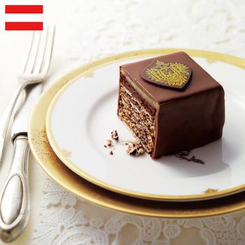 インペリアルトルテ ミニヨンダブルキューブ  ¥5,656(+8% ¥6,104)  もとは1863年に公爵の邸宅として建てられた、オーストリア ウィーンのインペリアルホテル。今もその厨房で手づくりされているオリジナルケーキです。極薄アーモンドケーキと上質チョコ、マジパンを5層にも重ね、極上のミルクチョコでカバー。そのおいしさに、ヨーゼフ皇帝が門外不出を命じたというエピソードは有名な話。