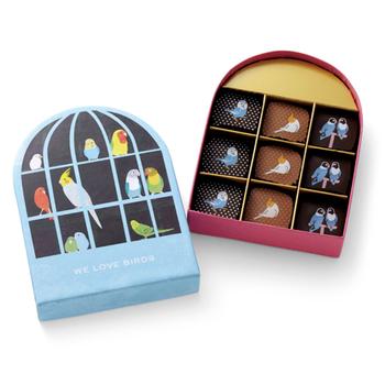 """鳥かご型ボックスも、ひと粒ひと粒にプリントされたインコも、""""かわいい!""""と、昨年大人気。チョコはもちろん、まろやかなプラリネやキャラメルガナッシュなどの本格ベルギーテイスト。  食べ終わったら、ボックスを鳥かごのようにつり下げて飾れるのも楽しい。"""