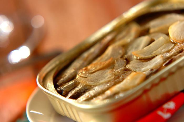 オイルサーディンを缶ごと焼いてしまうお手軽アヒージョ。缶を開けたらにんにくをプラスして焼くだけ、とっても簡単!おつまみにぴったりなアイデアですね。