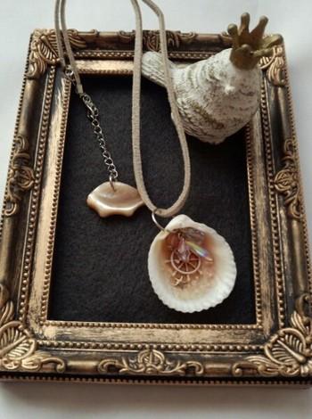 本物の貝殻に、着色したUVレジンやチャームを入れて固めたアクセサリー。hoichiさん作のものです。