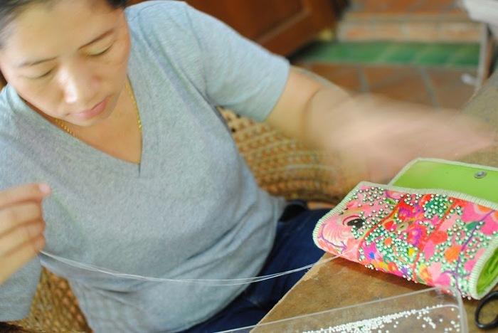 こちらはお財布のビーズつけの作業。ひと粒ひと粒、キラキラと光るビーズが手縫いでつけられていきます。