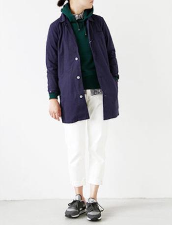 ネイビーがマリンな雰囲気のコート。インにパーカーを合わせてスポーティーなアクセントに。