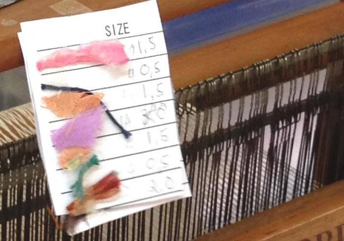 ホームの縫製場で服を縫製した後に残った端切れ布をどうにか生かせないかという考えから生まれたのが「裂き織り」。リボン状に裂いた端切れ布をつなぎ合わせて「裂き織り」のリボンを作り、それを織り機で丁寧に織り上げます。織る順番、色味や幅などを細かく決めて……