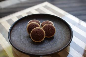 500円玉ぐらいの大きさで、真ん中の茶色い部分がチョコになっているちょっと変わった最中です。焼いてあるのでサクサクした食感で、香ばしいチョコが癖になる和洋折衷のお菓子です。