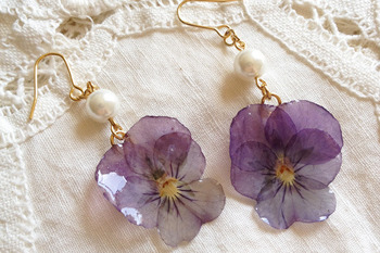 ビオラの押し花をそのまま閉じ込めたピアスはパールと合わせてより女性らしい印象に。コーディネートのアクセントとしてもコーディネートに華を添えてくれそうですね。