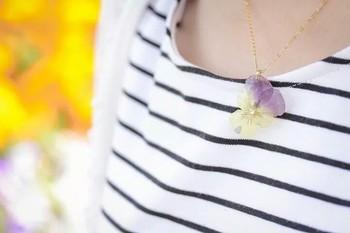 本物のビオラの花びらを樹脂で固めたネックレス。 淡いイエローとパープルの優しいコントラストが可憐な印象です。 シンプルなファッションに身につけるだけで、そっと華をそえてくれます。