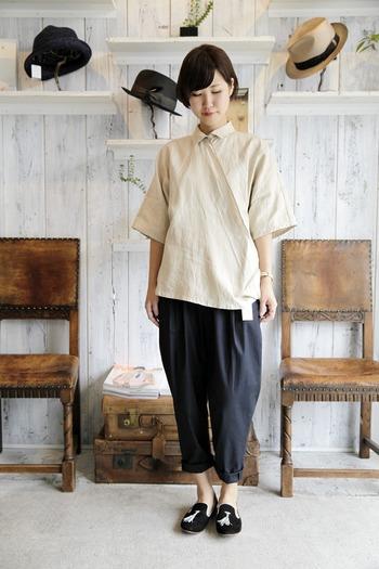 リネン100%で作られたシャツは、たてにボタンを配置するのではなく、生地を斜めに腰もとで留めるデザイン。シンプルながら個性の光るアイテムです。