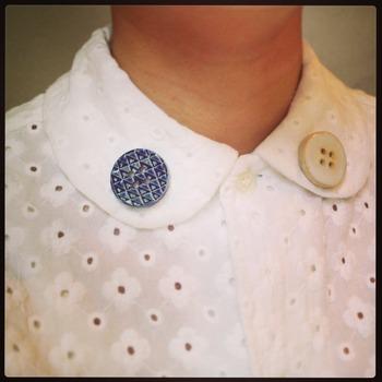 maitopartaの作品で一番らしさを堪能できるのはピンブローチやブローチではないでしょうか?こちらはボタンのピンブローチ。こんな風に襟元に留めると、いつものお洋服の雰囲気がガラリと変わっちゃいます。