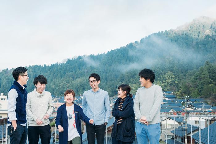 メンバーは、関西からこの地に移住した6人の若者たち。きっかけは2004年に福井豪雨の被災地支援のアート活動として開催された「河和田アートキャンプ」。「芸術が社会に貢献できることは何か」という問いを合言葉に全国から32大学の学生が参加しました。このイベントに参加することで、河和田の人々との交流が始まり、やがて河和田を含む鯖江市のものづくりの現場に魅了されてしまった彼らは、それぞれ、鯖江市で職を見つけ、新たな生活のスタートを切ります。そして「TSUGI」のメンバーとなった後も、肩書は、木工職人、眼鏡職人、デザイナー、鯖江市職員など様々。だけど、「ものづくり」に関わり、鯖江が大好きという点は大きな共通項として、皆に通じています。