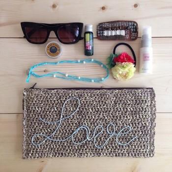 ラフィア風のクラフト糸で編んだクラッチバッグです。ブルーのLOVEの文字が爽やかでキュート。海に行きたくなるような一品です。