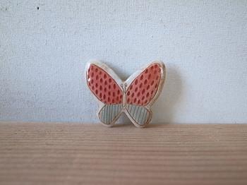 赤とグレーのコントラストが個性的な蝶のブローチです。小ぶりでも存在感がたっぷりで、その日のスタイルのポイントになること間違いなしです。