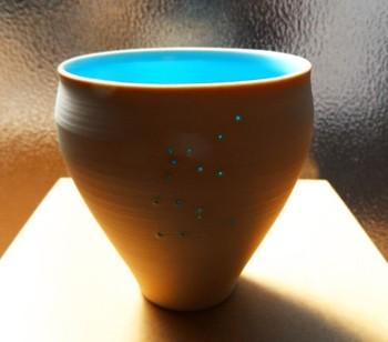 内側のブルーが鮮やかな星座カップです。表面に星座の形をなぞって小さな穴が空いており、陽の光が入ると、星座が浮かび上がります。内面のブルーが開けた穴を通して光が漏れ、その美しさは見惚れるほどです。(この作品は、みずがめ座(1/20~2/18)です)