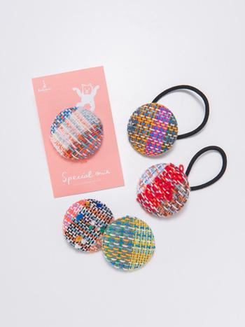 """""""なないろくるみヘアゴム"""" hickory03travelersデザインの、キレイな色彩のくるみボタンは、障がいを持つ人の自立支援をしている「special mix」の商品です。手織りの織物から作られているので、ひとつひとつ柄が異なります。"""