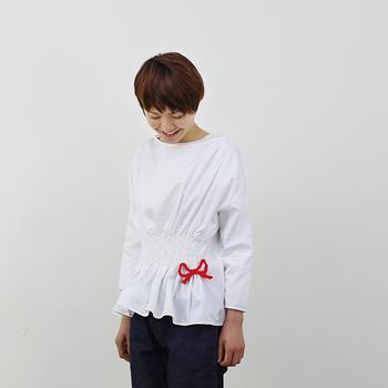 大き目のリボンブローチは、あえて腰あたりにつけることで、可愛さUP! 白のブラウスに、赤色が映えていて、とっても素敵。