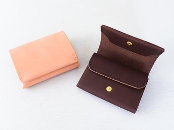 お札を縦に収納するつくりの二つ折り財布。 開閉はボタン式で、本体のフタ・小銭入れのフタの2ヵ所。