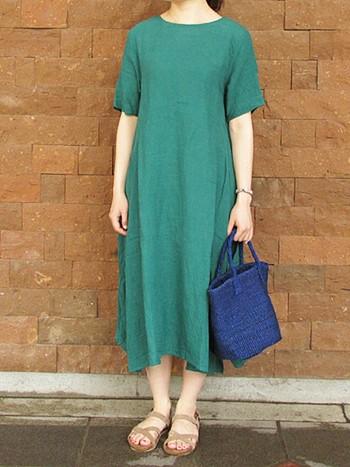 きれいなグリーンのワンピース。一枚でもさまになります。ブルーのバッグがポイントになっています。足元はサンダルで涼しげに。