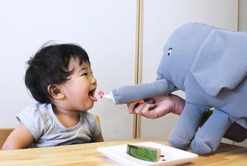 こちらは食事の時に大活躍の「ナナメがけゾウ」。  肩に斜め掛けできるよう、ヒモが付いていて鼻の先にあるベルトに指を通せば鼻を動かすことができるのです。 鼻先のベルトにフォークを通せば、まるでゾウさんがご飯を食べさせてくれてるみたい。