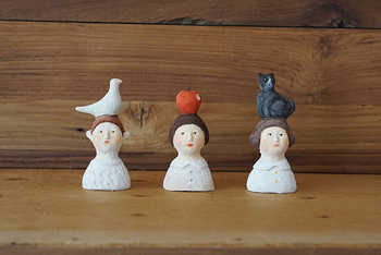 見ると思わずほほえんでしまう、にしおゆきさんの陶製人形です。 りんご、鳩、黒猫が頭の上にのったユニークなデザイン。お人形のなんともいえない表情がシュールでくせになるかわいさ。