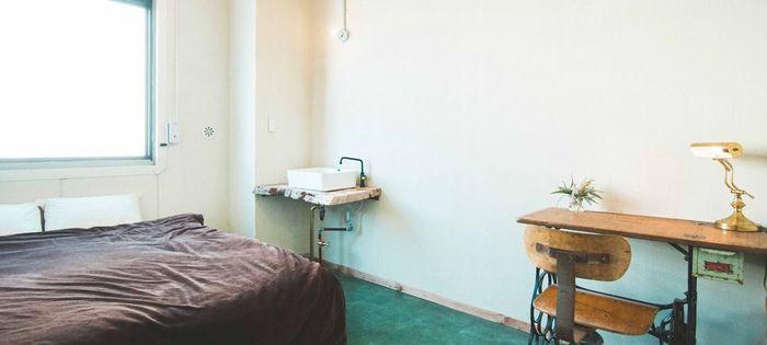 クイーンサイズの大きめのベッドが置かれた二人用の個室。机、椅子、洗面台が設置されています。