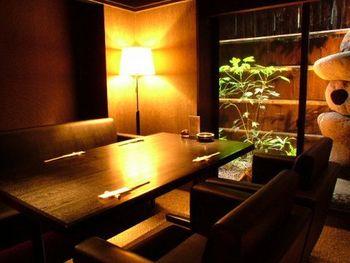 個室を中心とした客席が並ぶ造りです。落ち着いた雰囲気作りのため全体的に照明が暗めで、かわりにランプやテーブルライトを多用しています。