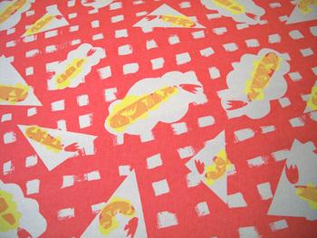 赤のギンガムチェックのようなデザインにのった、細長い黄色と赤の柄。よーく注目してみると…