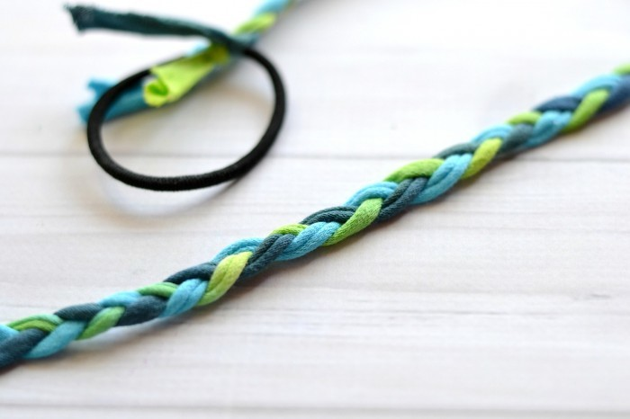 5. (4)のチューブを三つ編みしていきます。(ドアノブなどの固定された場所にヘアゴムをひっかけるとやりやすいです。) 6. 頭の周囲の長さまで三つ編みが完成したら、編み終わりをヘアゴムの反対側につなげ、余分なチューブをカットします。