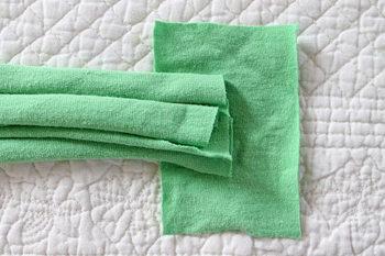 9. 頭の周囲に合わせて余分なパーツをカットします。パーツをつなぎ合わせるために、余ったTシャツの布で6.5×9センチくらいの四角いパーツを1枚作製します。