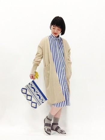 夏らしいストライプのワンピースに、ロングカーデを羽織れば涼しくなってもOKのスタイルに。お気に入りの夏ワンピを長く着られる方法です。