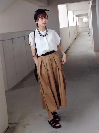 白ブラウス×ベージュのスカート。 ボリュームのあるボトムスが涼しげです。ブラウスも中に入れて着ることですっきりとした印象になります。