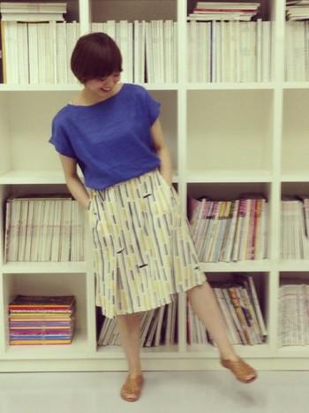 海のようなブルーのブラウスにかわいいテキスタイルの膝丈スカートを合わせて、夏らしいスタイルに。オフィスカジュアルにも良さそうです。
