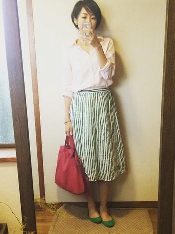 緑のストライプのリネンスカート。 白いシャツに緑の靴のバランスも素敵ですね。さし色に赤い鞄がとても似合っています。