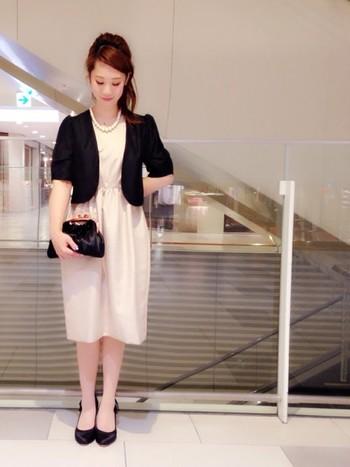 ミルキーピンクのドレスに、ブラックのボレロを合わせたコーディネート。シンプルなデザインのドレスに、かちっとしたフォルムのボレロと組み合わせ、フォーマルを押さえた、清楚なパーティーコーデです。