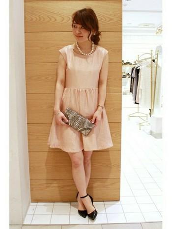 淡いピンク色が可愛らしいドレス。シンプルなデザインなので、個性的なビーズのパーティーバッグがポイントになって引き立っています。