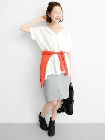 白のトップスにグレーのタイトスカートといった夏らしい爽やかなコーデ。そんなコーデに差し色として少し深みのあるオレンジのカーデを合わせてみて。肌寒い時には羽織って、暑い時には腰に巻くとアクセントにもなりますよ。
