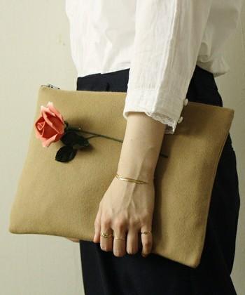 一瞬バラを一輪持っているかの様にみえる、ユニークなブローチ付きクラッチバッグ。とってもオシャレです。大きなブローチは存在感が際立ちます。