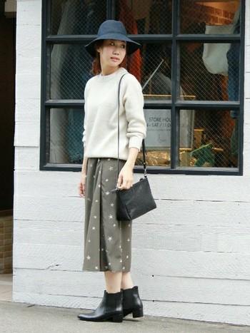 シンプルなニットに、星の模様が散りばめられたスカートを合わせたシンプルカジュアルなスタイル。サイドゴアブーツや、帽子とバッグを黒で統一させると大人っぽくまとまります。