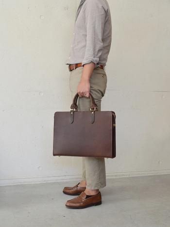 直線とプレーンな盤面できちんとした印象、革の質感が映える書類鞄。 サイドにはドイツホックと呼ばれる金具が付いています。