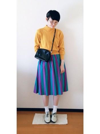 ハイネックのからし色ニットは、一枚あると長く使えるアイテムです。青と紫のストライプギャザースカートに合わせて、レトロガーリーに。